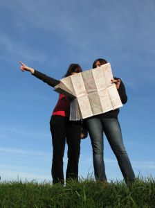 Two women lost, one pointing, the other holding a map.